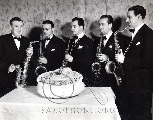 Richard Himber (left) posing with a recently patented Selmer-U. S. Padless saxophone and the saxophone section of his famous Studebaker Champions Orchestra